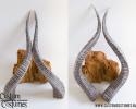 Puntoortjes gemaakt van zwarte hoogglans schubben gemaakt met latex. Iedere schub is met de hand gevormd en elk product is dus uniek. <br /> Deze oortjes schuif je over je eigen oren heen en plak je vast met huidlijm.